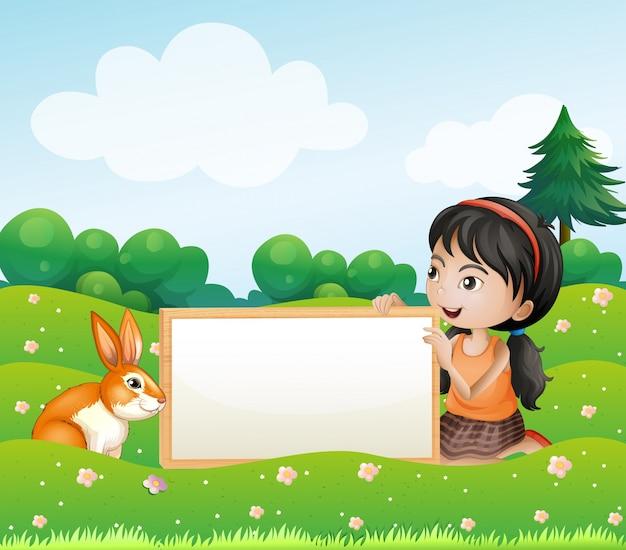 Dziewczyna trzyma pustą deskę z królikiem