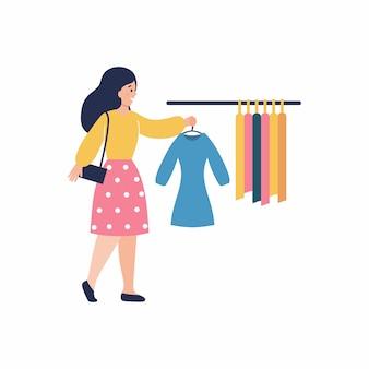 Dziewczyna trzyma sukienkę na wieszaku. wieszak na ubrania. sklep odzieżowy dla kobiet. płaski charakter wektor. uroda i moda.