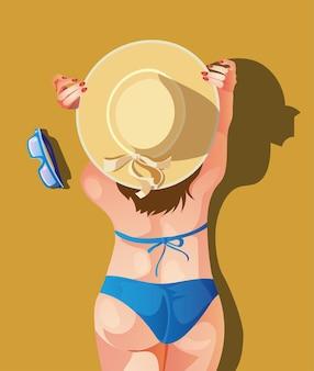 Dziewczyna w kapeluszu i kostiumie kąpielowym odpoczywa leżąc na brzuchu. kobieta odpoczywa, widok z góry.