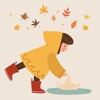 Dziewczyna w żółtym płaszczu przeciwdeszczowym i czerwonych butach wypuszcza papierową łódkę kałuża po deszczu