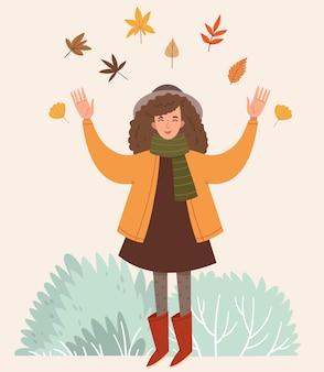 Dziewczyna wskakuje w jesienne liściejesienny nastrój dzieciństwo szczęśliwa dziewczyna