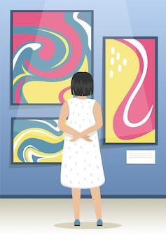 Dziewczyna wygląda na obrazy współczesnych artystów abstrakcyjnych. muzeum sztuki nowoczesnej. biennale sztuki współczesnej. minimalistyczne wnętrze muzeum.