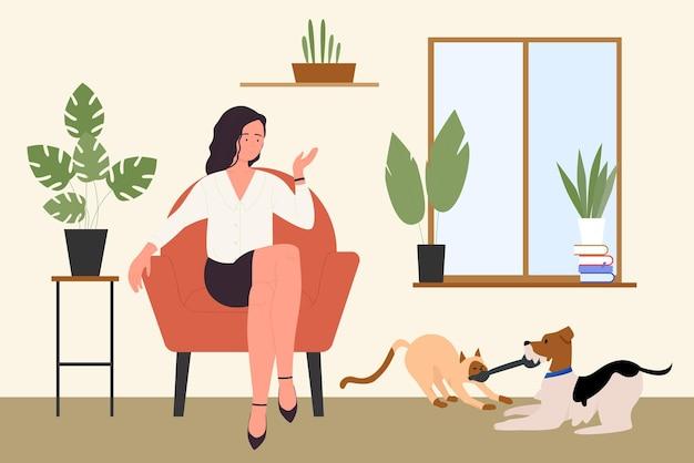 Dziewczyna z bawiącymi się kocimi i psimi przyjaciółmi zwierząt domowych młoda kobieta właścicielka zwierzaka siedzi na krześle