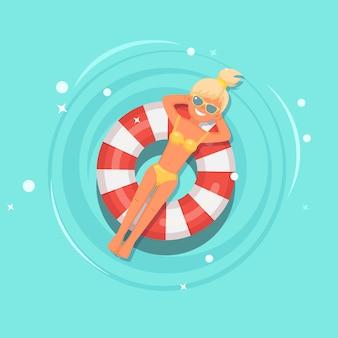 Dziewczyna z uśmiechem pływa, opalając się na dmuchanym materacu, boja ratunkowa w basenie.