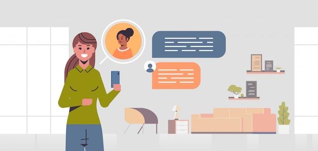 Dziewczyna za pomocą smartphone sieci społecznościowej czat bańka komunikacja koncepcja