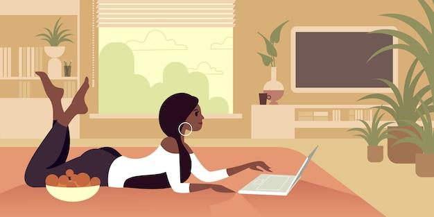 Dziewczynka boso leży na podłodze z laptopem i miską owoców.
