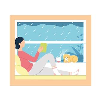 Dziewczynka czyta książkę i pije kawę / herbatę przy oknie, podczas gdy na zewnątrz pada deszcz