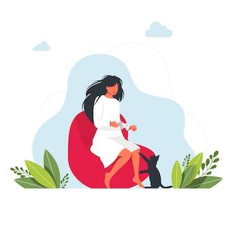 Dziewczynka siedzi na pufie i sięga po nią kot. kot chce zająć się dziewczyną. koncepcja pobytu w domu. brunetka dziewczyna siedzi i wyciąga rękę do kotka. słodki kotek. wektor