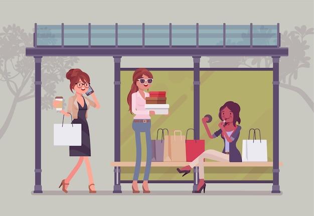 Dziewczyny na przystanku autobusowym po wielkich zakupach. panie ze sklepu z zakupami, pasażerki czekają na transport publiczny z pudełkami na prezenty. ilustracja kreskówka styl