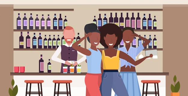 Dziewczyny robienie zdjęć selfie na aparacie smartfona ludzie relaksujący w barze picia koktajli barman obsługujących klientów nowoczesnej kawiarni wnętrze poziome portret