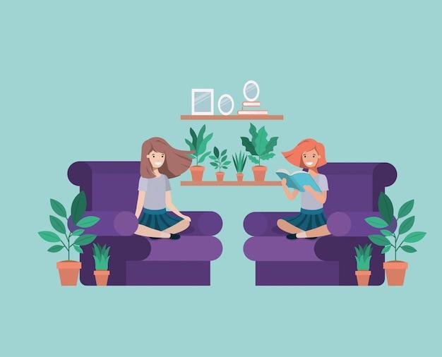 Dziewczyny studenckie siedzi czytanie książki w salonie