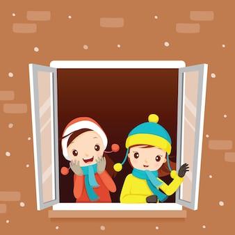 Dziewczyny w oknie, padający śnieg, sezon zimowy