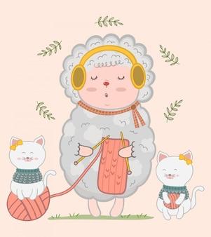 Dziewiarskie śliczne małe owce i dwa małe koty.
