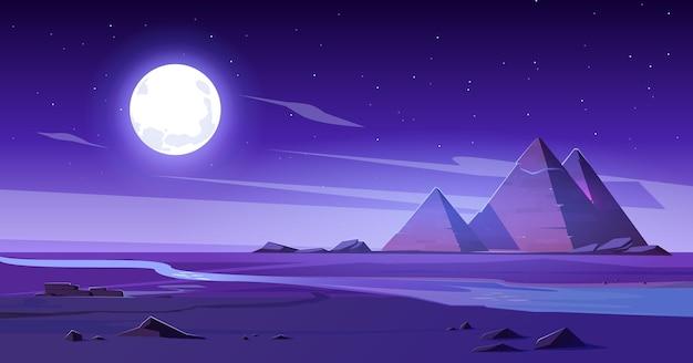 Egipska pustynia z rzeką i piramidami w nocy.