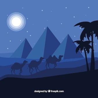 Egipski pustynny noc krajobraz z piramidami i karawaną