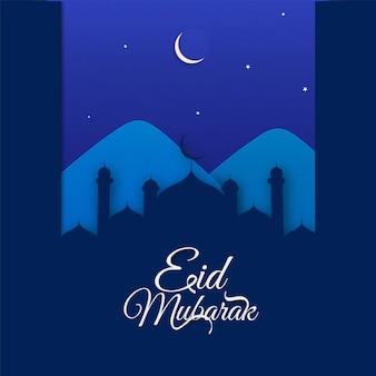Eid mubarak z wyciętym z papieru meczetem i górą w niebieską noc