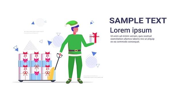 Elf Santa Pomocnik Ciągnięcie Wózka Wózek Z Prezentowymi Pudełkami Wesołych świąt Szczęśliwego Nowego Roku Ferie Zimowe Ilustracja Koncepcja Uroczystości Premium Wektorów