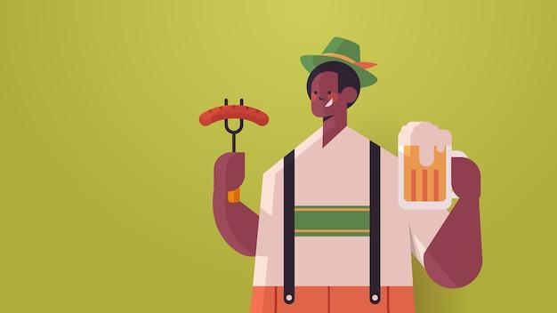 Facet jedzenie kiełbasy i picie piwa koncepcja partii oktoberfest afroamerykanin mężczyzna w niemieckich tradycyjnych strojach zabawy