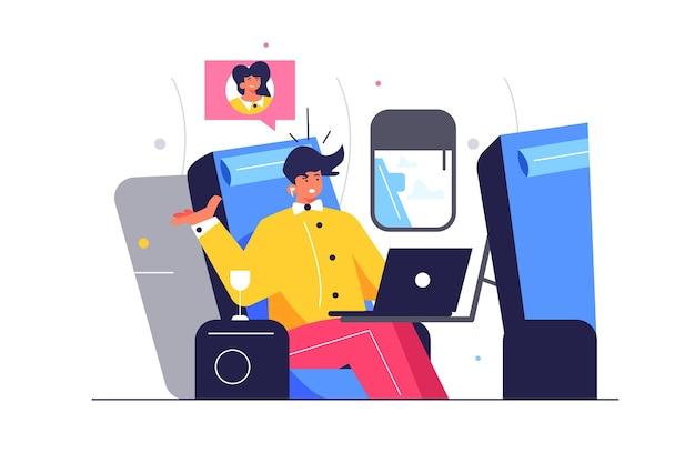 Facet rozwiązuje sprawy biznesowe w samolocie za laptopem, iluminator, facet siedzi na siedzeniu