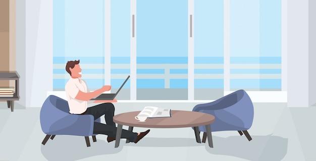 Facet siedzi na fotelu za pomocą laptopa szczęśliwy człowiek freelancer pracuje w domu nowoczesny salon wnętrze poziome pełnej długości mieszkanie