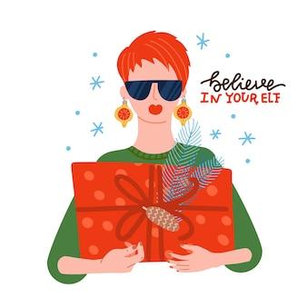 Fajna młoda dziewczyna w okularach przeciwsłonecznych i bombkach jako kolczyki z świątecznym pudełkiem w dłoniach świąteczna...
