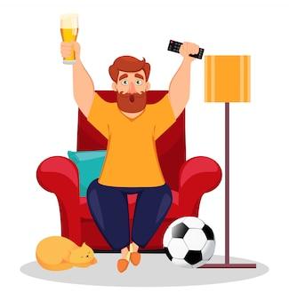 Fani sportu siedzą w fotelu i oglądają telewizję