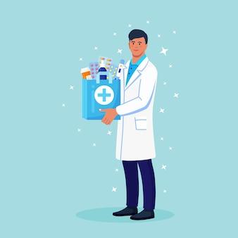 Farmaceuta trzyma w rękach papierową torbę z lekarstwami, lekami i butelkami z pigułkami. internetowa usługa apteki z dostawą do domu. lekarz w białym fartuchu ze stetoskopem