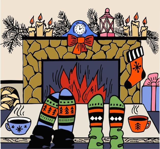 Ferie. stopy w wełnianych skarpetkach przy świątecznym kominku.