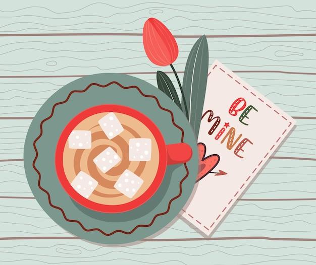 Filiżanka kawy z kartą miłości i tulipanem na drewnianym stole