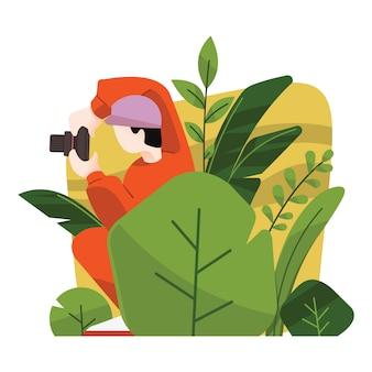 Fotograf ukrywa się w krzakach biorąc zdjęcie