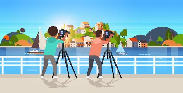 Fotografowie podróżni biorący zdjęcie natury górskich facetów z miasta na wyspie za pomocą aparatu dslr na poziomym tle statywu
