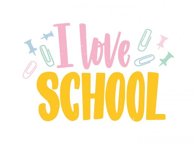 Fraza i love school napisana kolorową kaligraficzną czcionką i ozdobiona rozrzuconymi spinaczami i pinezkami.