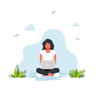 Freelance, nauka online, koncepcja pracy z domu. dziewczyna siedzi z laptopem w pozycji lotosu. dziewczyna siedzi w pozycji lotosu i pracuje na laptopie z rośliną domową w tle.