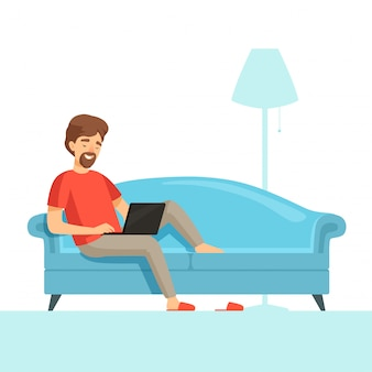 Freelancer na kanapie. szczęśliwy uśmiech pracy facet na wygodnym łóżku z laptopem