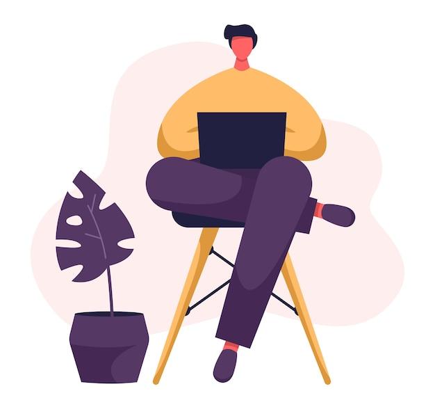 Freelancer pisze na swoim notebooku. młody mężczyzna pracujący w domowym biurze z laptopem na kolanach