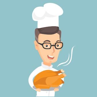Główny kucharz trzyma pieczonego kurczaka.