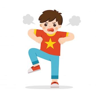 Gniewny wyraz. chłopiec wyraża gniew. wściekłe dziecko stojące w pozie marszczy brwi, krzyczy, uśmiecha się i pompuje pięści. znęcanie się dziecka