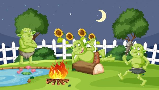 Gobliny lub trolle z ogniem noc kempingowa w stylu cartoon na tle ogrodu