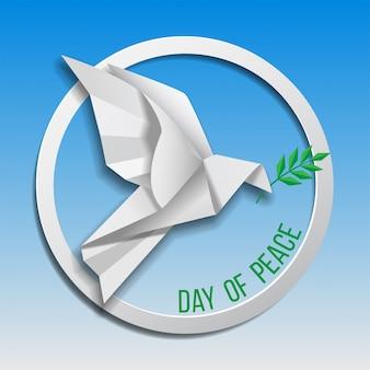 Gołąbek pokoju z gałązką oliwną latające na niebieskim tle. międzynarodowy dzień pokoju. papierowe origami.