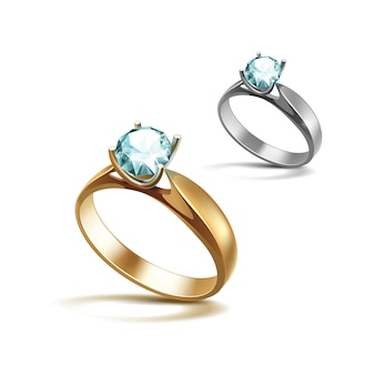 Gold and siver engagement rings with light turquoise shiny clear diamond close up isolated on white