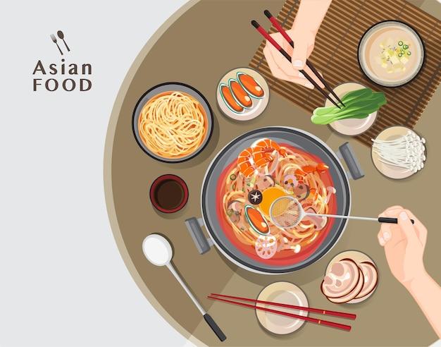 Gorący garnek w restauracji, ręka trzymająca pałeczki jedzenie shabu shabu