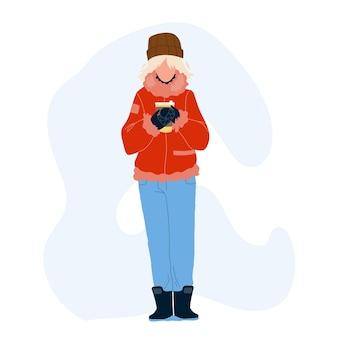 Gorący napój pijąca kobieta w zimowy dzień wektor. młoda dziewczyna ubrana w ciepłe ubrania sezonowe trzymając kubek gorącego napoju kawy lub herbaty. ocieplenie postaci z napojami płaska ilustracja kreskówka