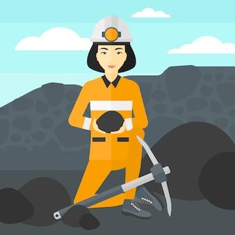 Górnik trzyma węgiel w rękach