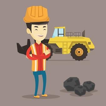 Górnik z dużym ekskawatorem w tle.