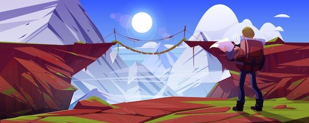 Górski krajobraz z turystą i mostem wiszącym nad przepaścią w skałach