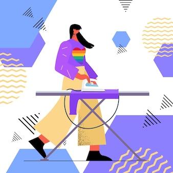 Gospodyni domowa prasowanie ubrań kobieta ubrana w tęczowy sweter lgbt transpłciowa miłość koncepcja prac domowych