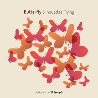 Gradientowa motylia sylwetki latający tło