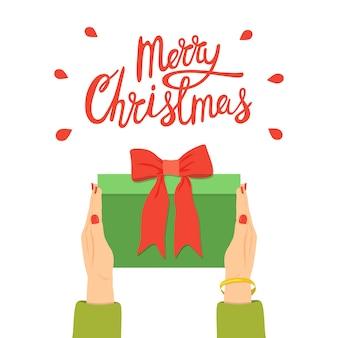 Gratulacje wesołych świąt. kobiece ręce trzyma pudełko z kokardą. dać prezent