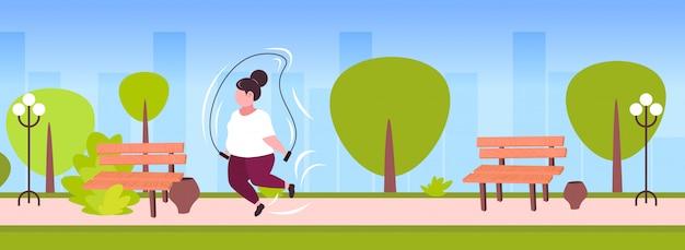 Gruba otyła kobieta robi ćwiczenia ze skakanką nadwaga dziewczyna trening cardio trening utrata masy ciała koncepcja lato park krajobraz