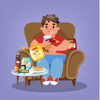 Grubas siedzi w fotelu i je fast food
